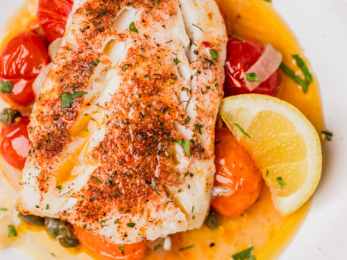 baked cod placed on juicy cherry tomatoesserved with a lemon wedge.