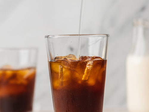 a hand pouring water over iced cold brew.
