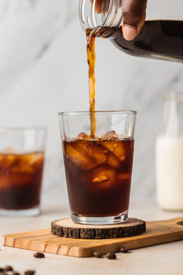 a hand pouring coffee over ice in a glass cup.