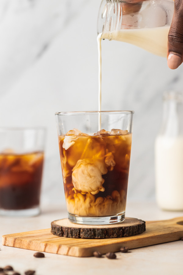 A HAND POURING MILK OVER ICED COFFEE.
