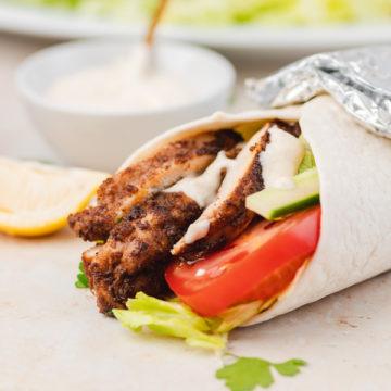 chicken shawarma wrap placed beside a pot of yogurt tahini sauce.
