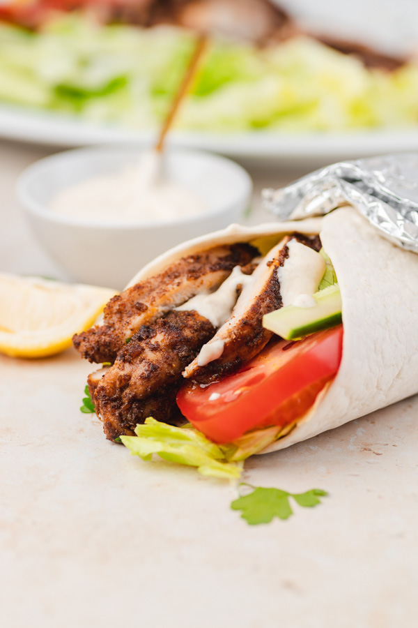 flavourful and juicy shawarma chicken in a wrap with salad.