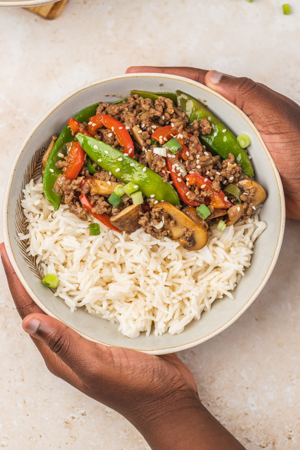 a hand holding up a bowl of beef stir fry and white rice.
