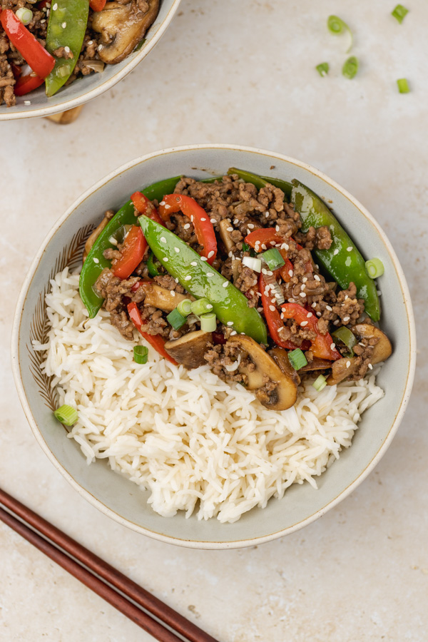 two bowls of stir fry with rice.