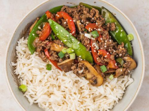a bowl of rice ground beef stir fry placed beside chopsticks.