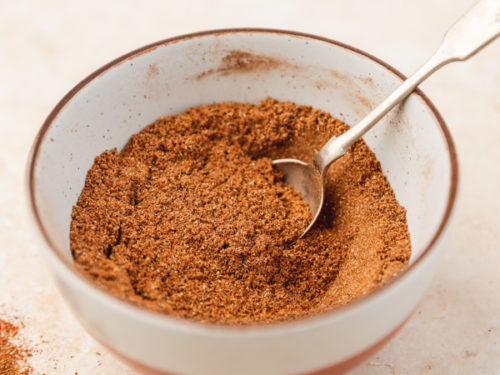 shawarma spice blend in a small ceramic bowl with a spoon.