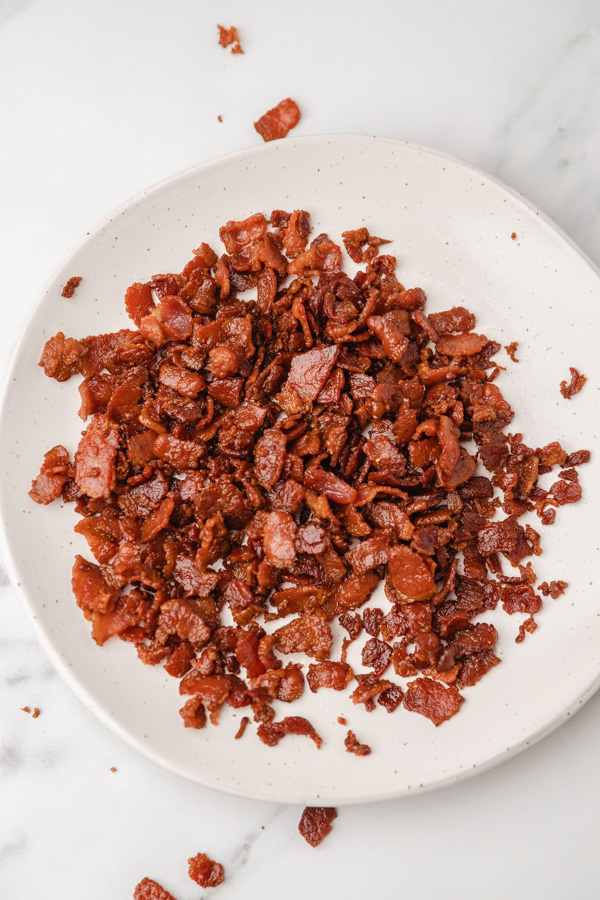 cooked bacon pieces on a small white plate.