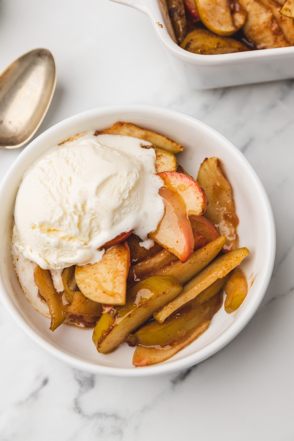 a bowl of baked apple with ice cream.