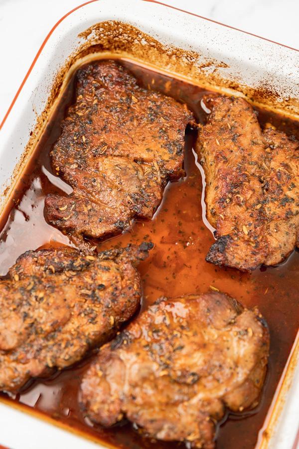 four juicy pork steak in a white enamel baking sheet.