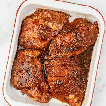 foru marinated pork steaks in a baking pan.