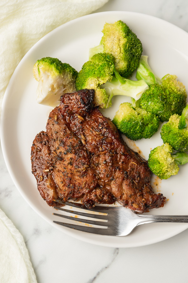 a white plate of steak and broccoli with a fork.
