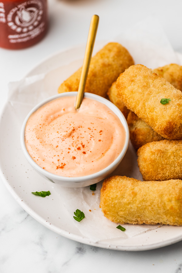 a plate of crispy potato croquette and a dipping sauce.