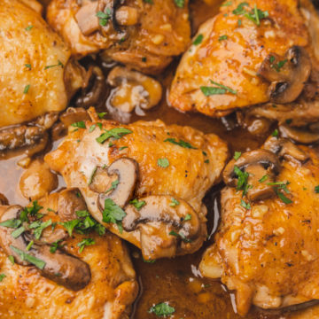 chicken thighs and mushrooms in a skillet.