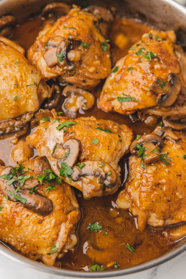 a close up of chicken thighs in a skillet.