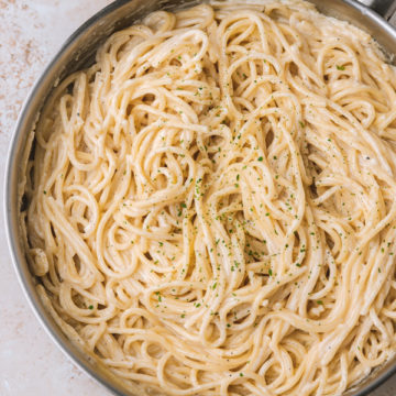 freshly cooked creamy spaghetti in a skillet.